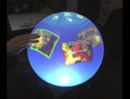 The sperical multitouch display is a homebrew internally projected image on a hollow polycarbonate sphere.  The multi-touch function is done with infrared (IR) lighting and camera.  A toolkit is underway for simple content delivery and interactivity (the prototype works with Flash).
